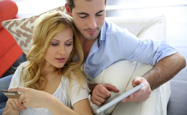 Couple at home shopping online easily with digital tablet