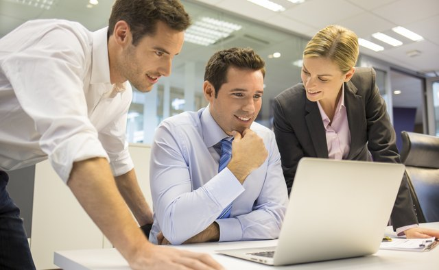 Business team of three in office and planning work