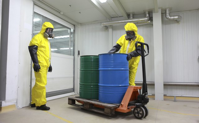 Two specialists dealing with barrels of chemicals