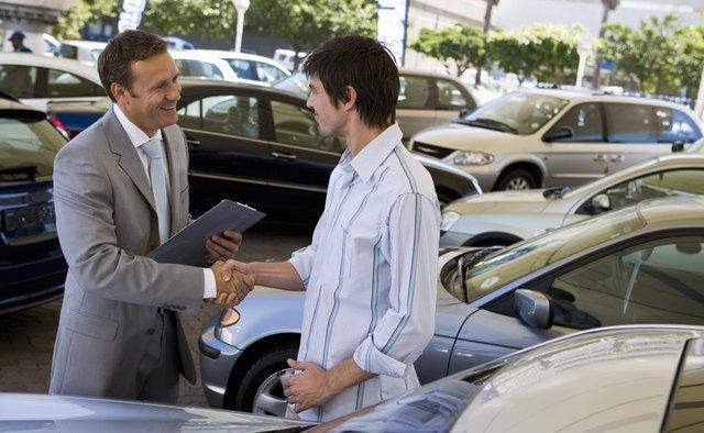 Salesman showing man a car