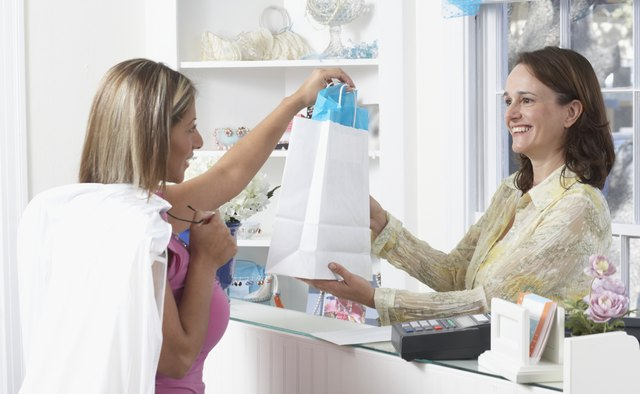 Saleswoman giving shopping bag to a young woman at the checkout counter