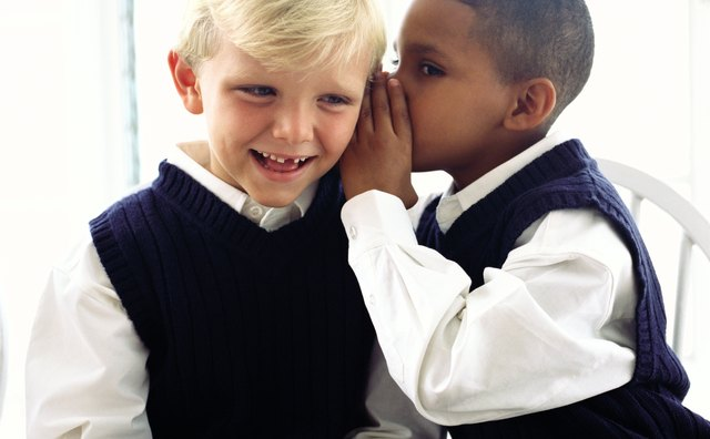 portrait of a boy (8-10) whispering to another at school
