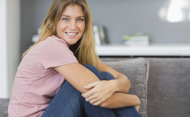 Smiling blonde sitting on her couch