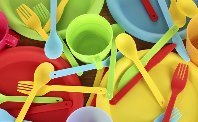 bright plastic disposable tableware on wooden background close-up