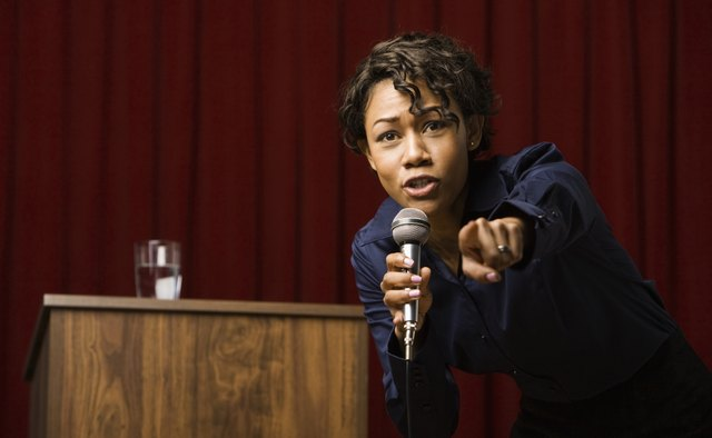 Mixed race businesswoman speaking on stage and pointing