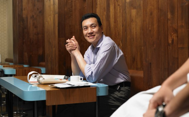 Man in restaurant by adlister, smiling at chef