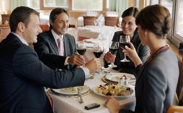 Two businessmen and women at restaurant table, raising glasses