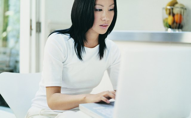 Woman Using a Laptop Sitting at Her Dining Room Table