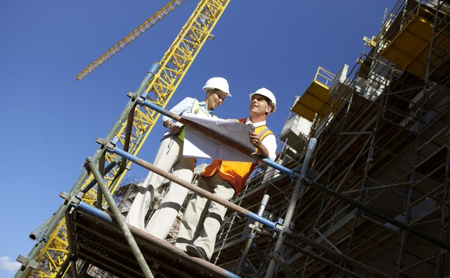 Two Well Dressed Colleagues Standing Side by Side on a Construction Frame, Looking at Blueprints