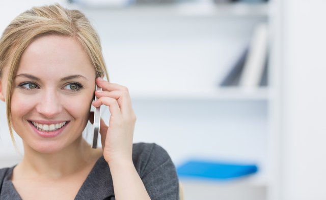 Close-up of business woman using mobile phone in office