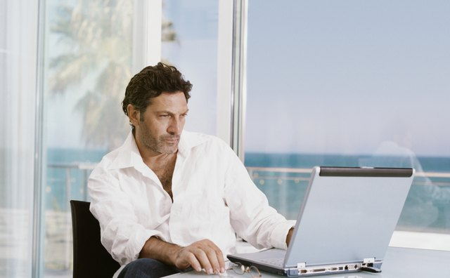 Mature Businessman Sits at a Table Indoors by a Patio Using His Laptop