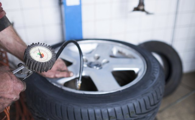 mechanic  checking the air pressure in a tyre