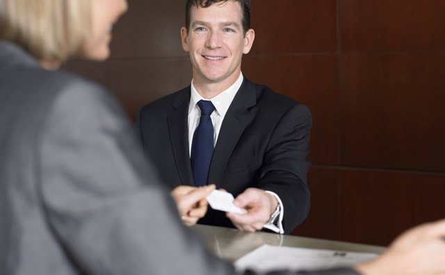 Businessman Giving a Receptionist His Business Card