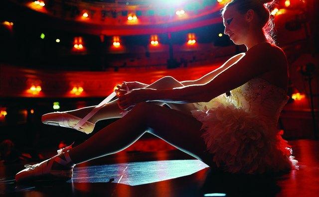 Ballet Dancer Sitting on Stage Tying Her Ballet Shoe