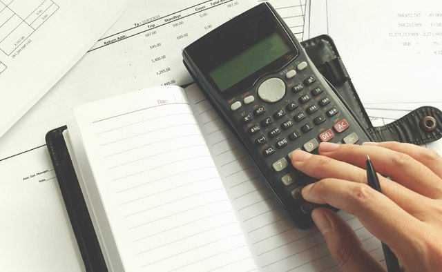 Cropped Hand Of Man Using Calculator On Desk At Office