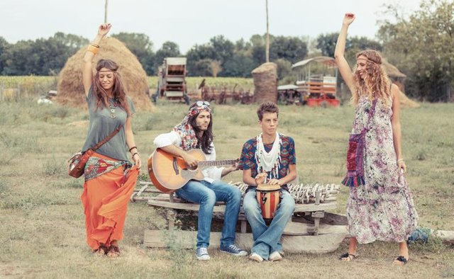 Hippies dancing and playing music in a field.