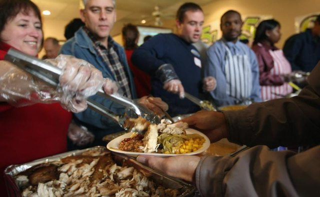Volunteers feed the homeless at Thanksgiving.