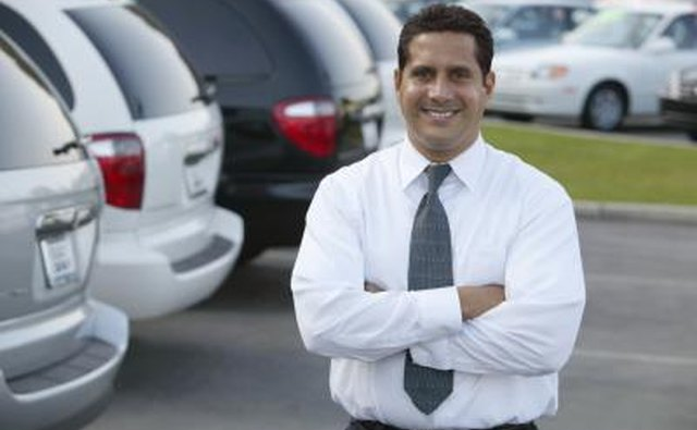 A car salesman stands in his dealership lot