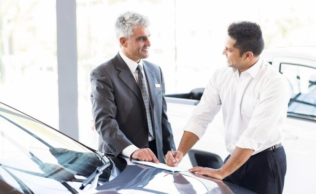 A customer discusses a lease agreement with a car dealer