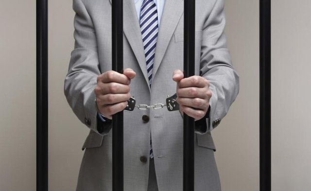 A man dressed in a business suit behind bars.