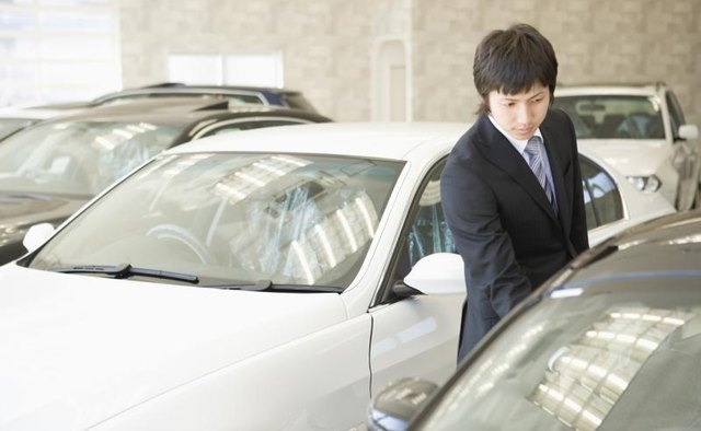 A car salesman inspecting one of his cars