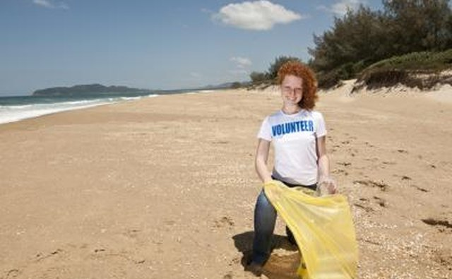 Young volunteer with garbage bag cleaning beach