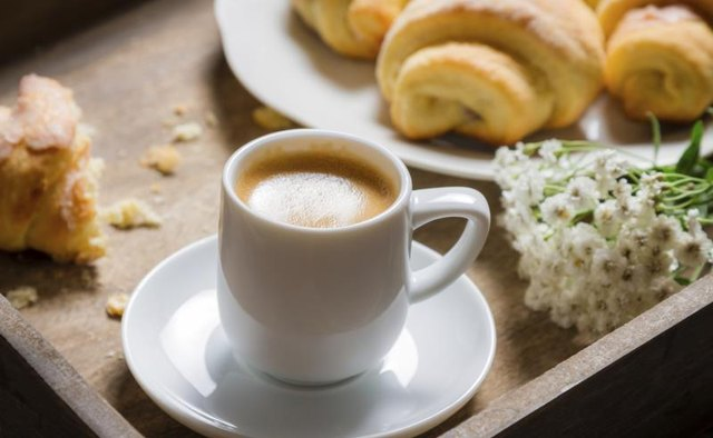 A cup of coffee on a tray next to a plate of croissants