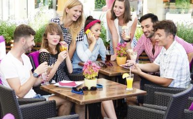 Social group of young adults meeting in sidewalk cafe.