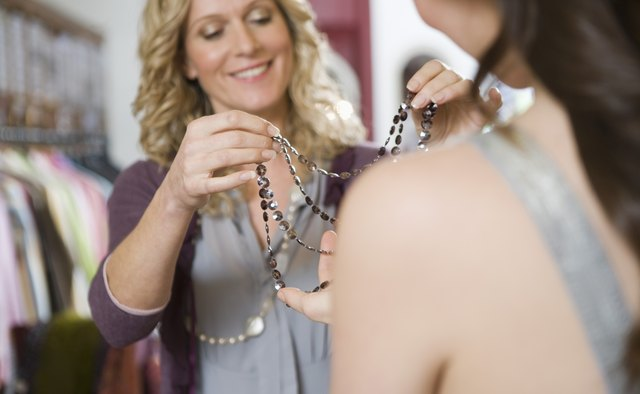 Smiling woman giving customer a necklace