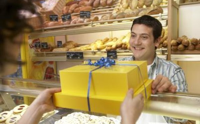 A baker hands a customer a gift wrapped package.