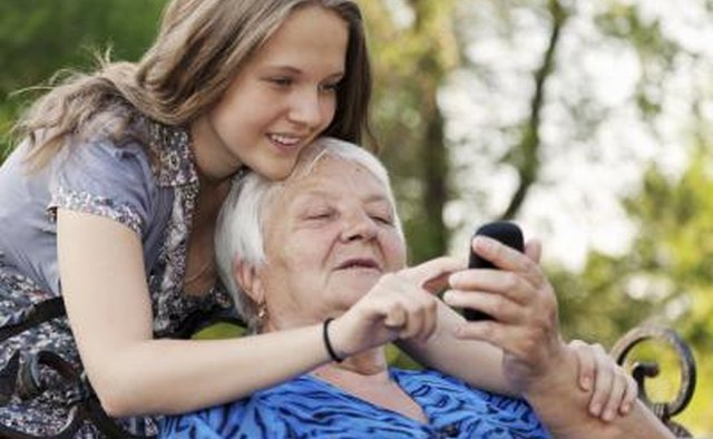 Preteen and senior looking at cell phone