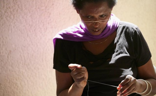 An African seamstress working with thread.