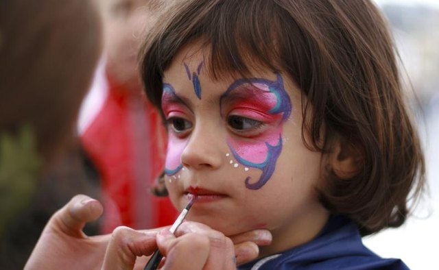 Little girl having her face painted