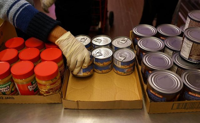 Volunteers stack items at a food pantry.