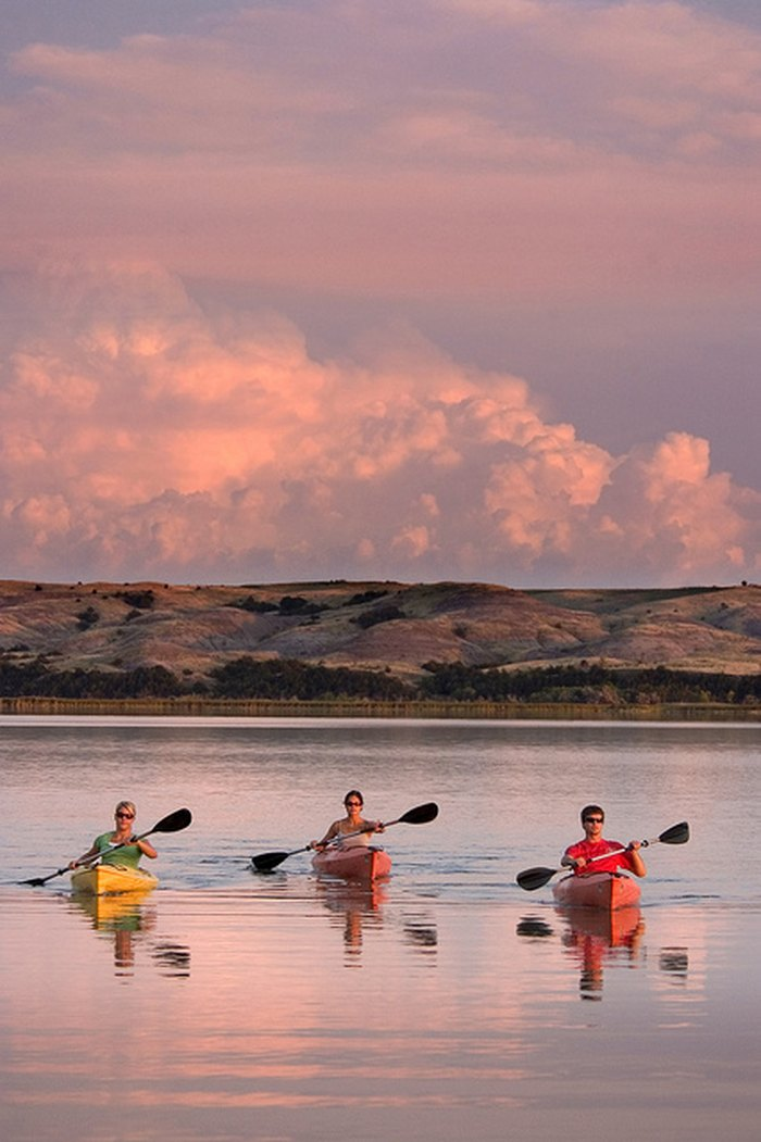 Three kayakers paddling on peaceful water