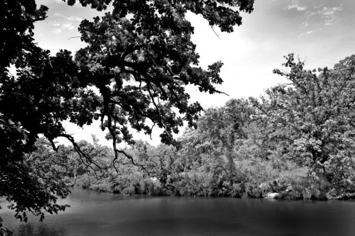 A greyscale photo of the waters near the waterfall.