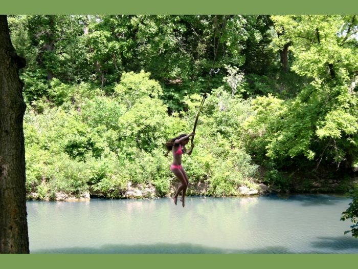 A woman in a pink bikini using a rope swing to drop into a deeper area of water at Pillsbury crossing.