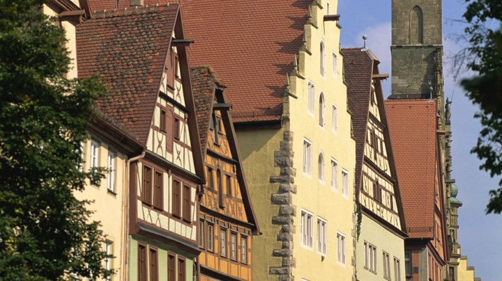 "You can travel between Munich and Rothenburg, Germany, by car, train or bus. Four or five towns in Germany are named Rothenburg, so make sure you're headed for Rothenburg ob der Tauber -- literally, ""red fortress above the Tauber"" -- in the Franconia region of Bavaria. This small, medieval village sits along the Romantic Road and is a major tourist destination during the summer travel season."