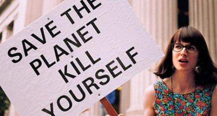 """Chris Korda en una manifestación sosteniendo un cartel que dice """"Salva al planeta, suicídate""""."""