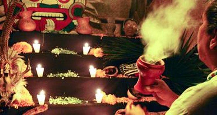 Un chamán prende incienso frente a un altar durante el Día de los Muertos.