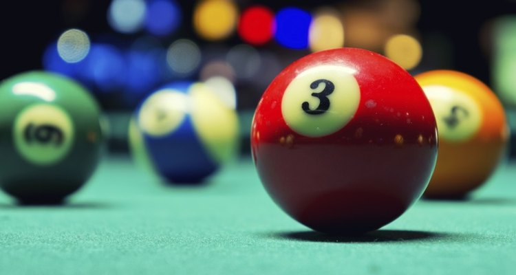 The felt of the pool table lets the ball roll smoothly.