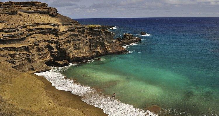Os cristais de olivina dão uma coloração verde à areia desta praia