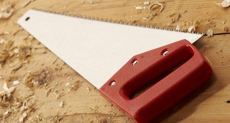 Corta madera con un serrucho.