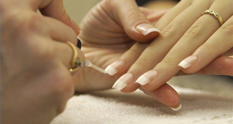 Aplica uñas acrílicas para una manicura francesa.