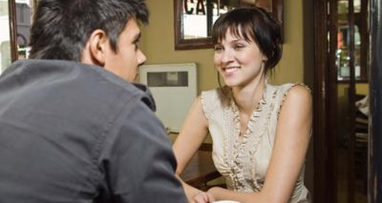 Smiling young couple talking in coffee shop.