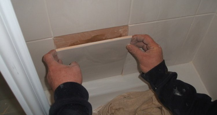 Placing the last tile on the wall of a tile bathtub/shower.