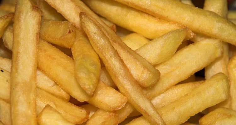 Bake frozen French fries with a touch of oil to give them a crispy texture.