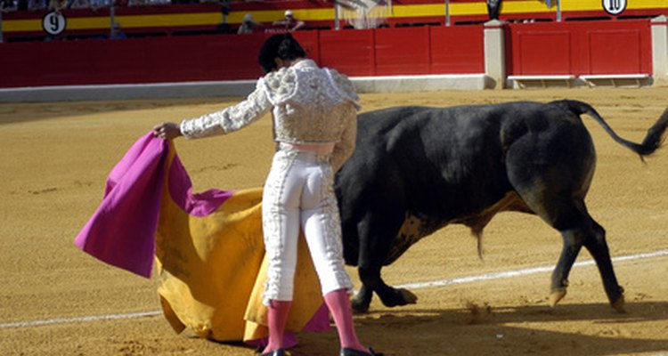 Bullfighter, wearing traditional pink socks and using a yellow-and-pink cape.
