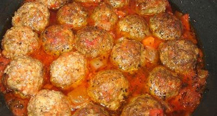 Cocina a fuego lento cocinando albóndigas en salsa de espaguetis para mejorar su sabor.