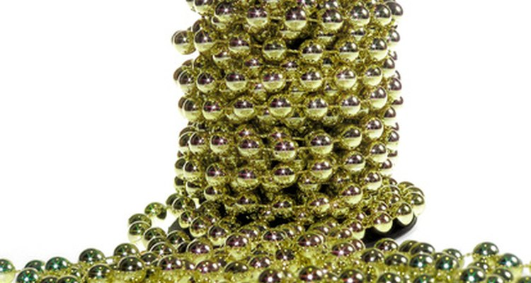 Decorate a cardboard egg with spray paints, rhinestones, gems and beads to style it in a Faberge egg design.